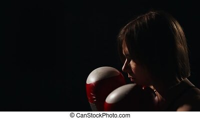 Muscular fitness girl training with his instructor to carry out strikes on the feet in Boxing gloves. The lesson of self-defense. A Boxing workout. Close-up