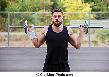 Muscular fitness handsome man workout with barbell
