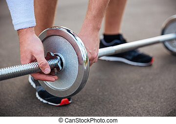 Muscular fitness man going to lift heavy barbell