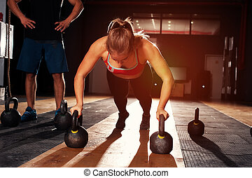 Muscular girl doing push ups with kettle bell