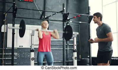 Muscular girl lifting heavy barbell under trainer's guidance...