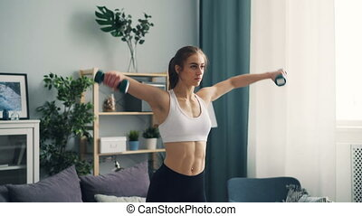 Muscular girl in top and leggings is lifting weight training with dumbbells in light flat focused on practice alone. Active lifestyle and modern youth concept.