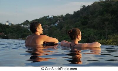 muscular guy approaches brunette leaning on pool edge and admiring hilly landscape with forests under summer evening sunlight