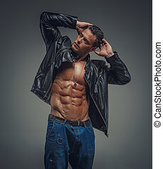 Muscular guy in jeans and black jacket