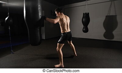 muscular handsome fighter giving a forceful forward kick...