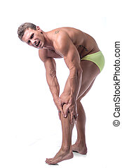 Muscular handsome man holding his leg and knee in pain