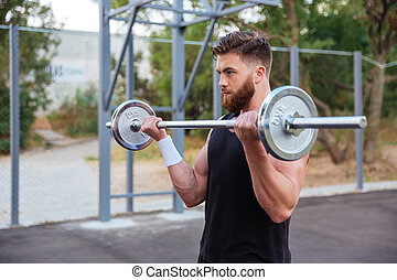 Muscular handsome man workout with barbell