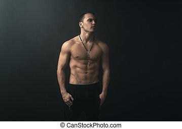 muscular, hombre, en, fondo oscuro