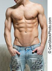 muscular, hombre, en, pantalones vaqueros rasgados, estantes, cerca, el, sofá