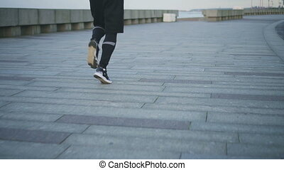 Muscular legs of male jogger on embankment.