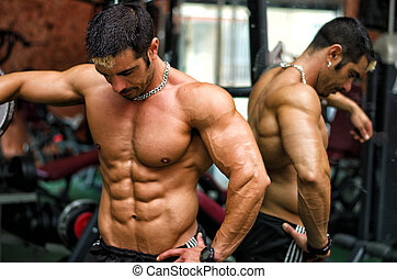Muscular male bodybuilder resting in gym during workout -...