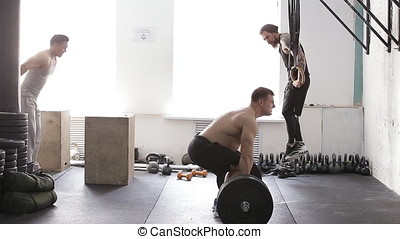 muscular male crossfit training. athletes train in the gym -...