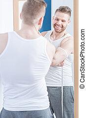 Muscular male measuring his biceps