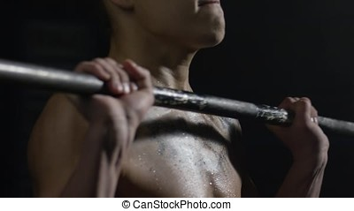 Muscular male model doing exercises with barbell. Fit young man lifting barbells, working out in a gym. Lifting barbells standing