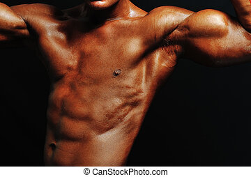 Muscular male torso of bodybuilder on black background