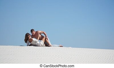 Muscular man and a beautiful girl lying on the sand in the desert