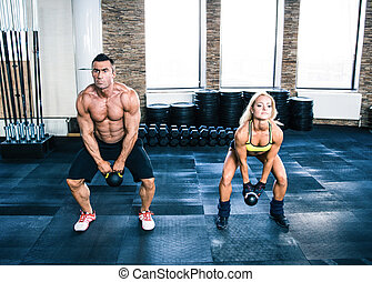 Muscular man and fit woman doing exercises with kettle ball
