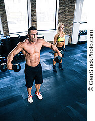 Muscular man and fit woman lifting dumbbells