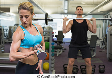 Muscular man and woman lifting weig