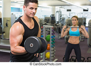 Muscular man and woman lifting weights