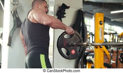 Muscular man bodybuilder in black tank top pick up a heavy dumbbell in a gym