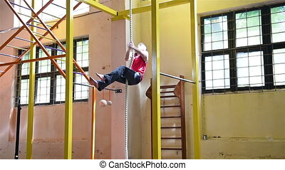 Muscular Man Climbs Rope At Gym. Slow Motion Effect