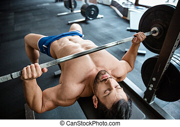 Muscular man doing bench press - Portrait of a handsome ...