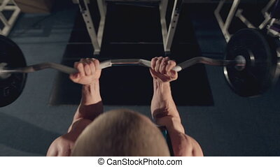 Muscular man doing exercise for biceps with a barbell in the gym