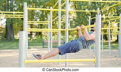 Muscular Man Doing Exercises on Horizontal Bar - Handsome...