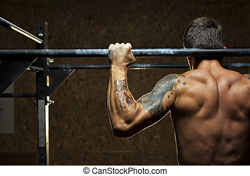 Muscular man doing pull up exercise on bar in gym