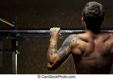 Muscular man doing pull ups exercise in gym