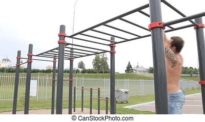 Muscular man doing pull-ups on horizontal bar