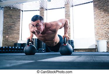 Muscular man doing push ups in gym - Handsome muscular man...