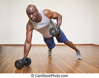 Muscular man doing push ups with dumbbells in gym - Full ...