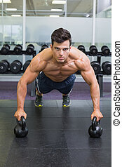 Muscular man doing push ups with ke - Portrait of a muscular...