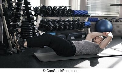 Muscular man doing sit ups in a gym