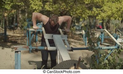 Muscular man doing triceps exercise at outdoor gym