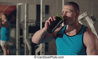 Muscular man drinking water after grueling workout
