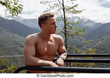 Muscular man during his outdoor workout in the mountains.