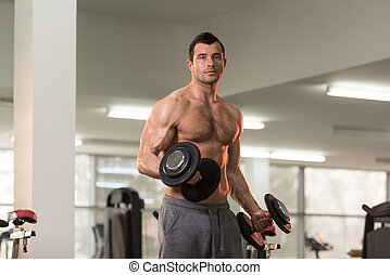 Muscular Man Exercising Biceps With Dumbbell
