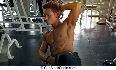 Muscular man exercising doing sit up exercise in gym