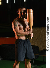 Muscular Man Exercising With Bowling Pin - Young Man Working...