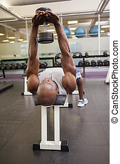 Muscular man exercising with dumbbell
