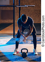 Muscular man exercising with kettle bell in gym