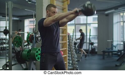 Muscular man exercising with kettlebell in gym