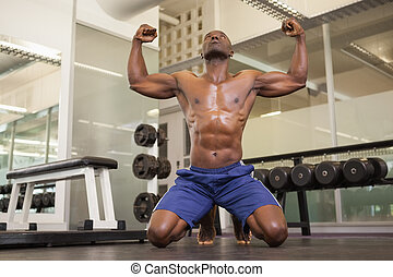 Muscular man flexing muscles in gym - Shirtless young ...