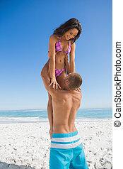 Muscular man holding his girlfriend