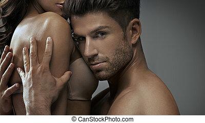 Muscular man hugging his sensual girlfriend - Muscular man...