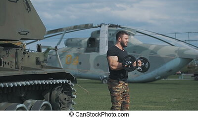 Muscular man in a military uniform has arranged training at...