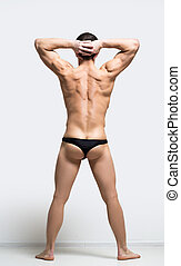 muscular man in a thong - Back view of handsome man with...